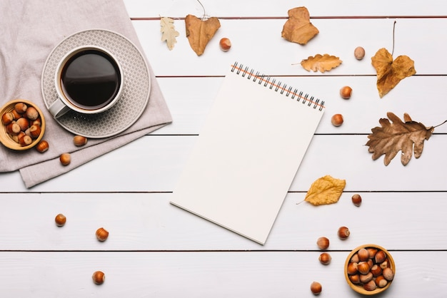 Notebook and leaves near coffee and nuts