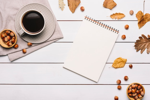Notebook and leaves near nuts and coffee
