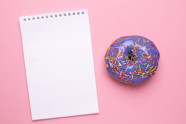 Notebook and lilac sweet donut on a pink background flat lay