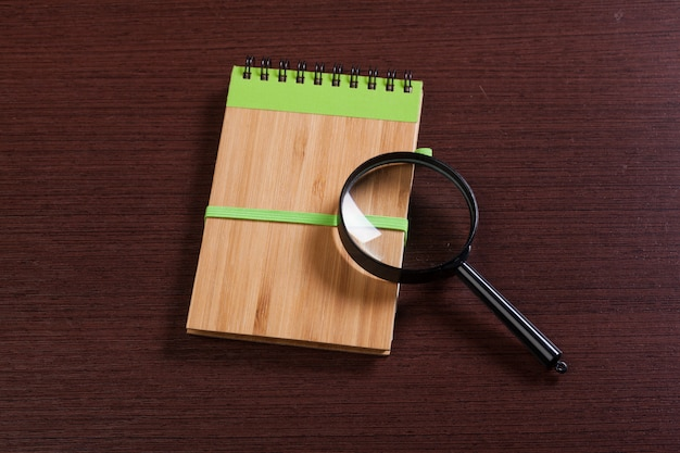Notebook and magnifier on a wooden surface