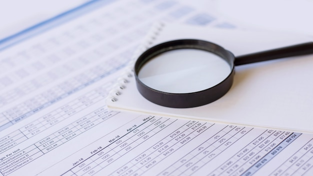 Notebook and magnifying glass over a business document
