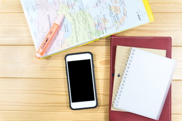 Notebook, map and smart phone on wooden table.