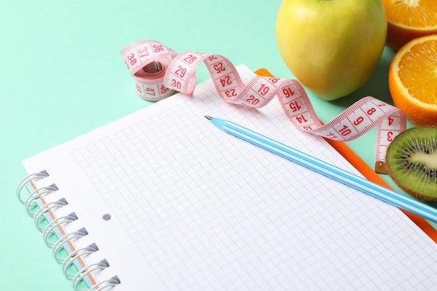 Блокнот, измерительная лента, ручка и вегетарианское питание. потеря веса