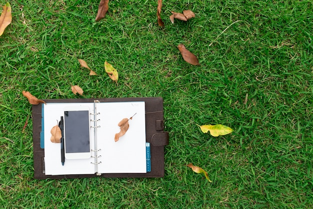 Notebook and mobile phones lying on green grass.