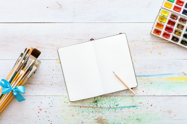 Notebook mock up with art supplies on white wooden creative table. top view