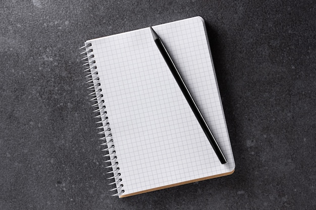 Notebook mockup. a5 paper with black pencil on black. top view.