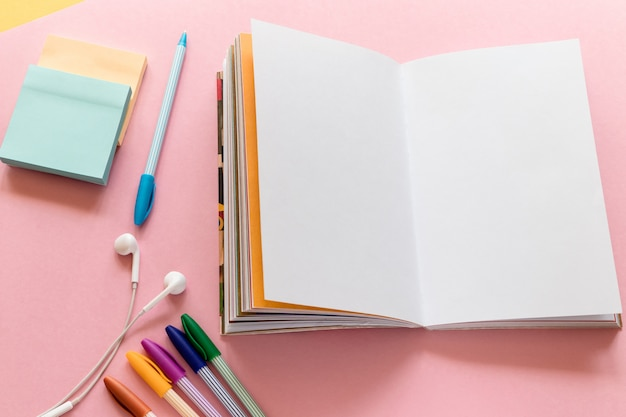 Notebook, multicolored pens and headphones on pink