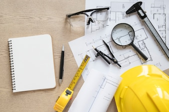 Notebook near blueprints and construction supplies