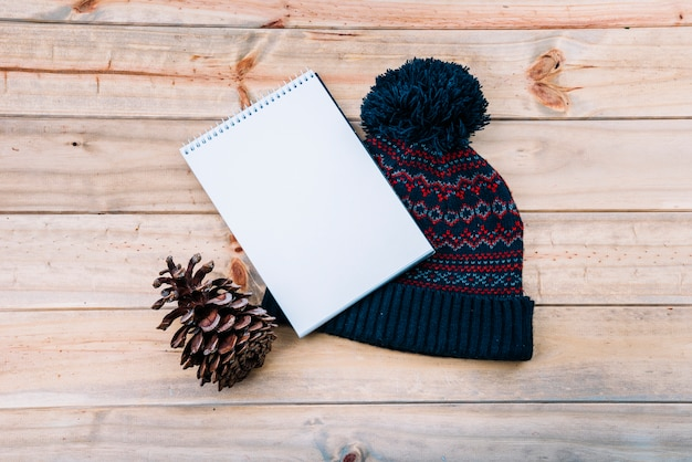 Notebook near bobble hat