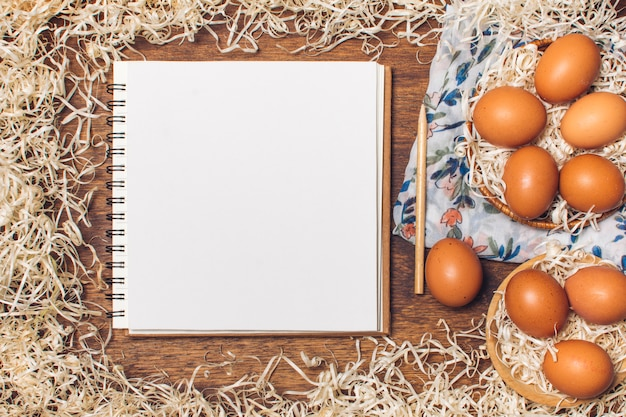 Notebook near chicken eggs in bowls on flowered material between tinsel on board