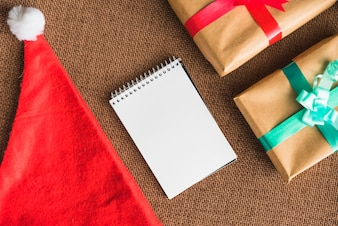Notebook near Christmas hat and present boxes