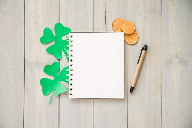 Notebook near coins and decorative clovers