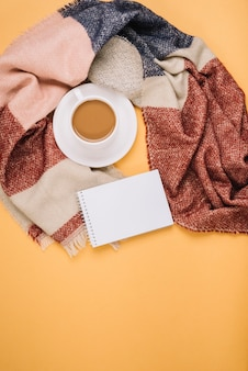 Notebook near cup and scarf