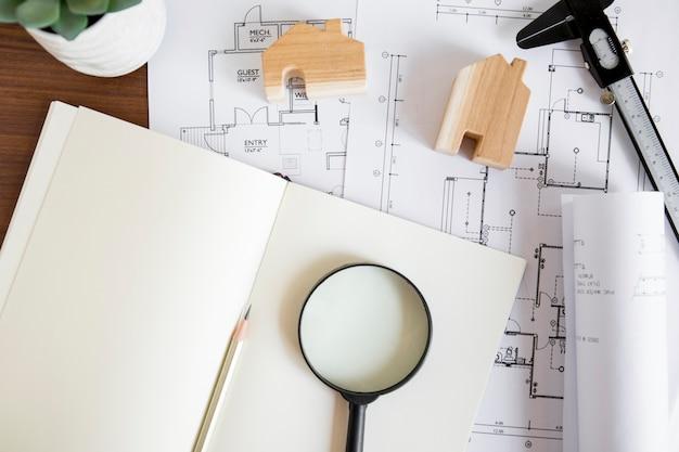 Блокнот рядом с чертежами и чертежами домов