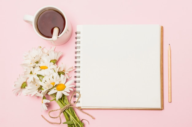 Notebook near flowers and cup of drink