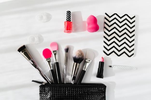 Notebook near makeup bag with cosmetics
