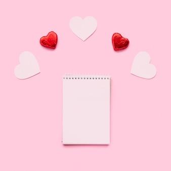 Notebook near ornament hearts