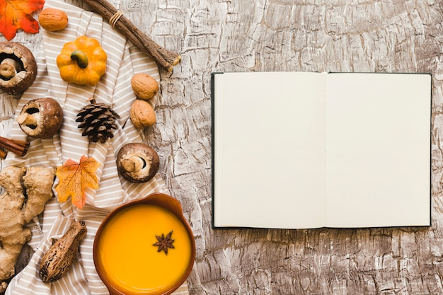 Notebook near soup and symbols of autumn