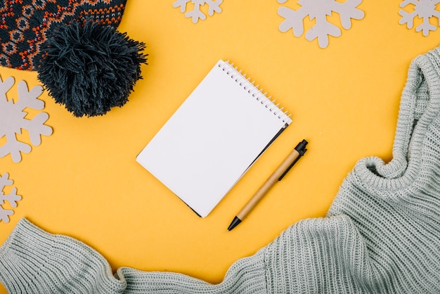 Notebook near sweater and bobble hat