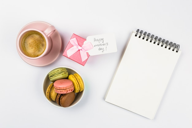 Notebook near tag with words on present, cup of drink and macaroons in bowl