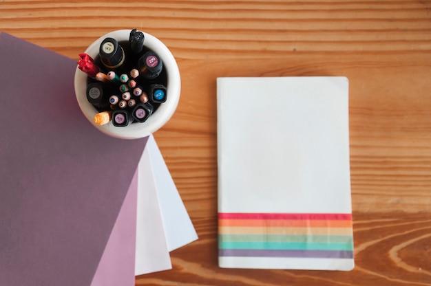 Блокнот рядом с пишущими принадлежностями и бумагой