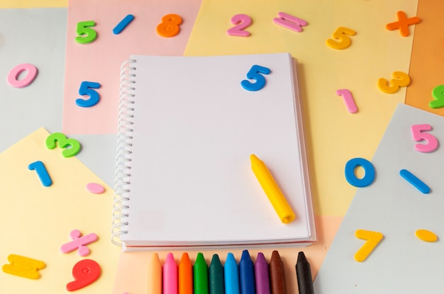 Номера ноутбуков и мелки на красочном фоне вид сверху