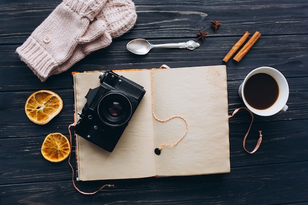 木製のヴィンテージテーブル上のカメラとコーヒーの思い出のノート。