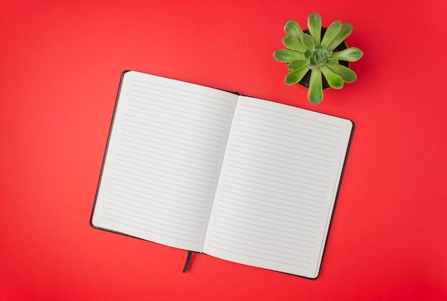赤いテーブルの上のノート。設計。最小限のコンセプト。フラットレイ
