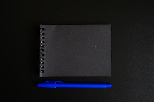 黒いシートと黒い背景に青いペンで春のノート。