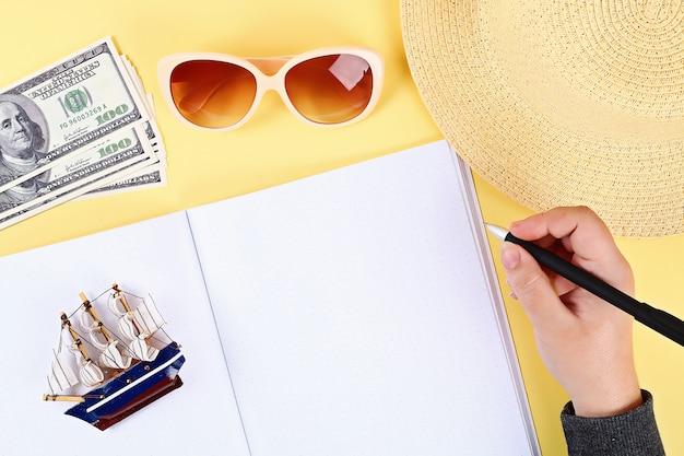 노란색 배경에 노트북입니다. 여름 개념. 휴가 준비.