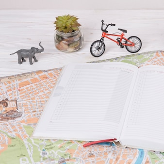 Notebook on map near toy animal and bicycle