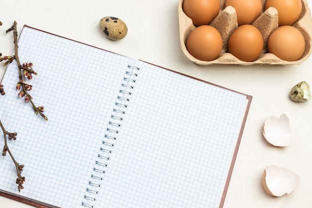 春のノート。カートンコンテナに茶色の鶏の卵。ノートブックの木の枝。テーブルの上のウズラの卵と卵殻。上面図。