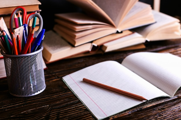 Notebook, open books and school supplies on a dark wooden table against the background of a chalk board