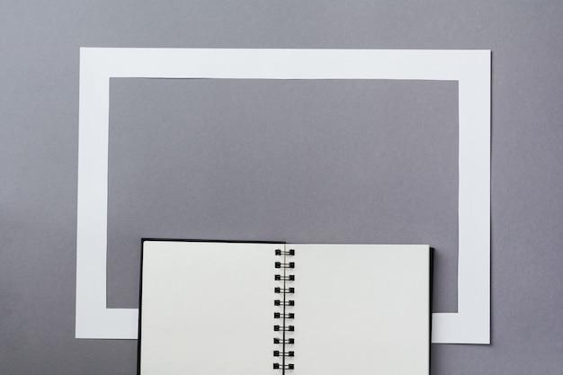 고전적인 파란색 배경에 노트북 또는 스케치북 및 종이 프레임. 아침 최소한의 개념입니다. 복사 공간이 있는 상위 뷰입니다.