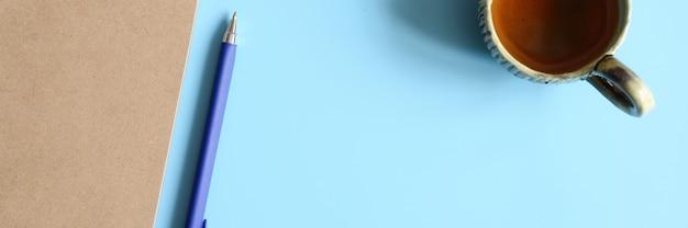 青の背景にクラフト紙とペンとティーカップで作られたノートまたはスケッチブック。テキスト用のスペース。バナー