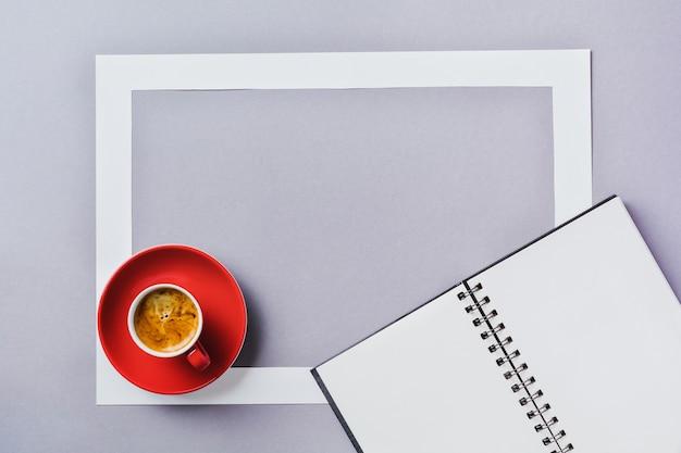 ノートまたはスケッチ ブック、クラシックな青の背景にコーヒーと紙のフレームと赤いカップ