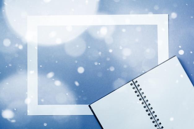 雪の影響で古典的な青色の背景に紙のカード フレームを持つノートまたはスケッチ ブック