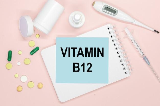 Страница записной книжки с текстом витамина b12 на столе с таблетками и шприцем. медицинская концепция.