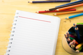 Notebook paper and color pencil on wooden table. Back to school.