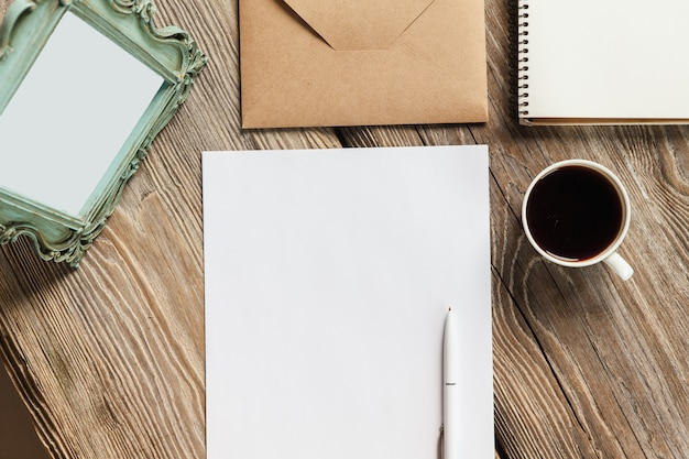 ノート、紙、コーヒーカップ、ヴィンテージの古い額縁の封筒