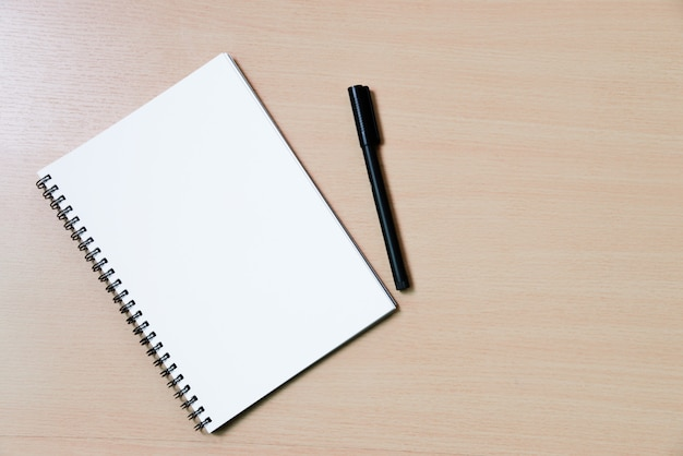 Notebook paper note with a pen on wooden desk