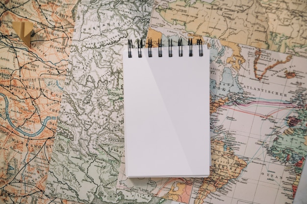 Notebook and paper plane on map