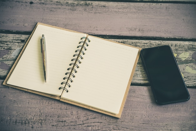 A notebook paper with a pen and smartphone on wooden table