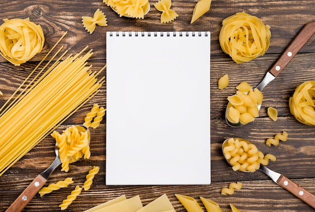 Notebook and pasta in spoons
