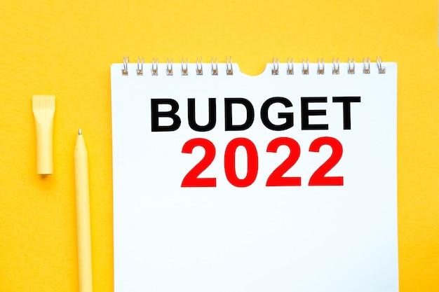 Блокнот, ручка и слова бюджет 2022 на желтом