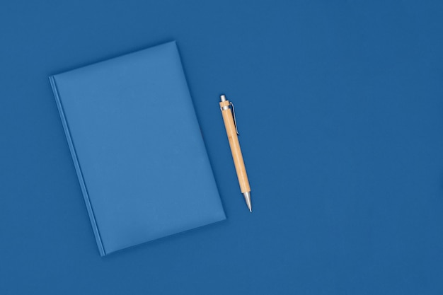 Notebook and pen on blue color. business concept. top view