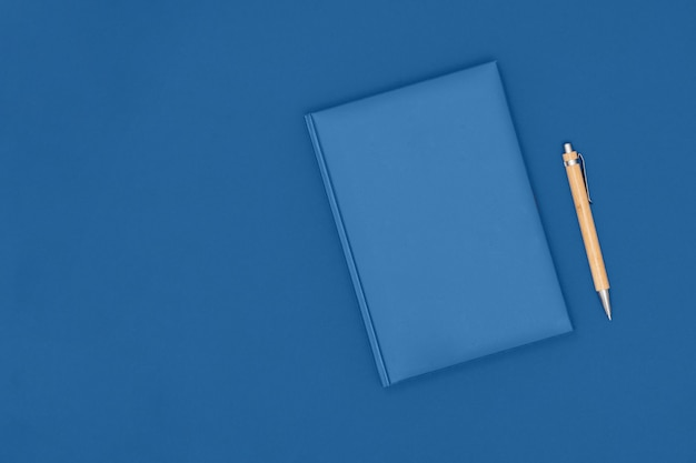 Notebook and pen on blue table. business concept.