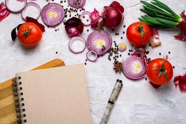 Блокнот, ручка, разделочная доска и овощи на светлом фоне.