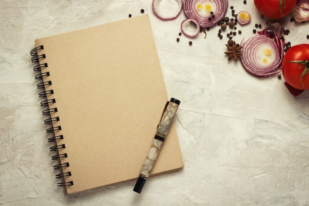 Notebook, pen, cutting board and vegetables on a light background.