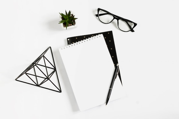 Notebook, pen, eye glasses lie on a white background